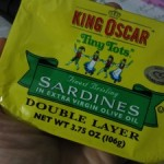 A can of King Oscar Sardines and a cell phone