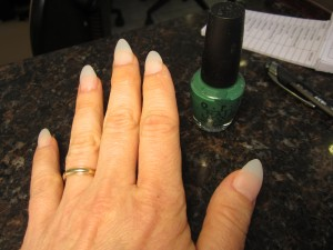 Painting the acrylic nails green.